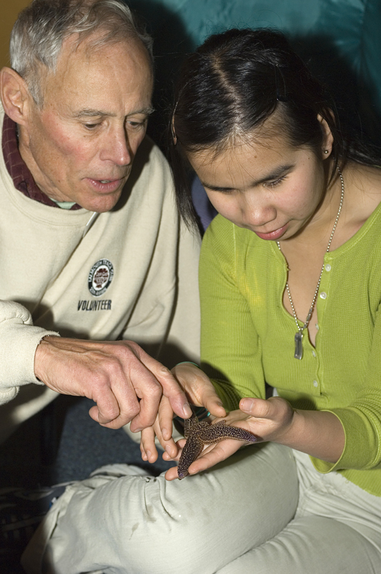 WHOI volunteer Rich Minor showing a star fish specimen to a young student