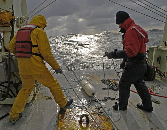 Veteran seagoing WHOI researchers Craig Marquette (left) and Will Ostrom deploy a mooring with tiny temperature probes from R/V Oceanus during a gale off Cape Hatteras