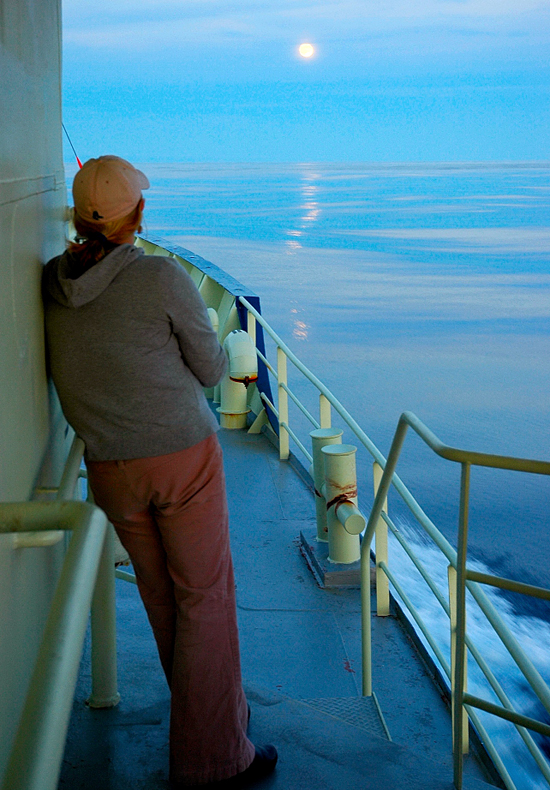 Messman Kathryn Eident, looks at the moon in the distance from the deck of R/V Oceanus.
