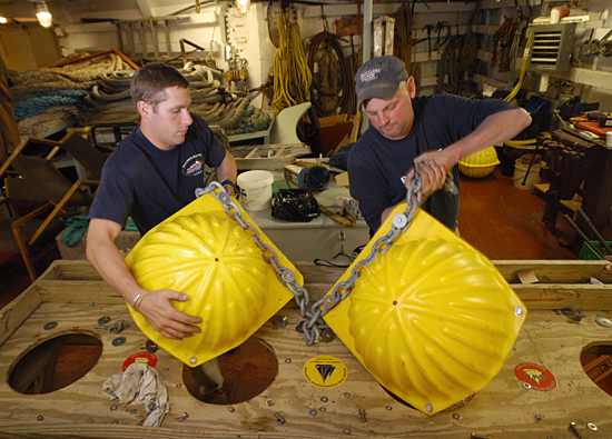 Kris Newhall and John Kemp examine and repair floats on board the Canadian icebreaker Louis S. St-Laurent.