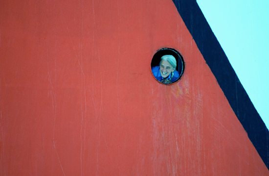From onboard the Canadian icebreaker Louis St-Laurent, Steward Judith Joncas peers out from a porthole.