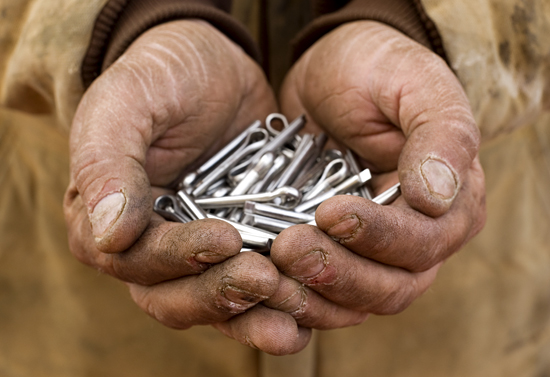 A handful of fasteners held by a crewman.