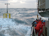 Researchers and crew members struggle to deploy a spar buoy in rough seas.