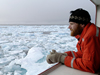 Jeremy Kaspar, a student at the University of Alaska, Fairbanks, keeps a watchful eye on the icy ocean from onboard USCG Healy.