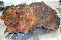Rusty-orange iron oxide coats the left side of this sample of seafloor rock