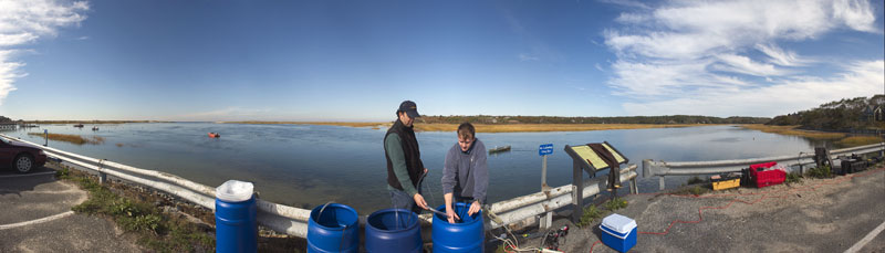 Assistant Scientist Jeff Donnelly holds a core of mud and sediment pulled up from a marsh.