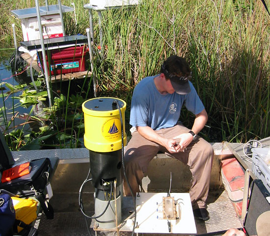 Research Assistant Matt Allen sits on an airboat and sets up a WHOI-designed automated seepage meter for a three-week deployment in the Florida Everglades.