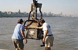 WHOI Senior Research Assistant Jay Sisson (left) and Engineer Craig Marquette maneuver a box corer after plucking a 30-centimeter-deep sample of sediment from the bottom of the Hudson River in June 2001.