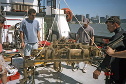 WHOI Assistant Scientist Peter Traykovski (left), Senior Research Assistant Jay Sisson, and a professional diver examine an instrument tripod covered with hydroids and mud after six months on the bottom of the Hudson River.