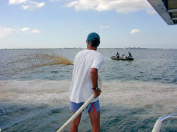 Scientist Mike Henry of the Mote Marine Laboratory sprays clay slurries into Florida's Sarasota Bay while WHOI Postdoctoral Investigator Mario Sengco and colleagues in the other boat track the dispersal of the plume with water sampling devices.