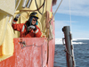 Working in open water in Antarctica's Ross Sea, Assistant Scientist Mak Saito deploys a water sampler from the R/V Nathaniel Palmer.