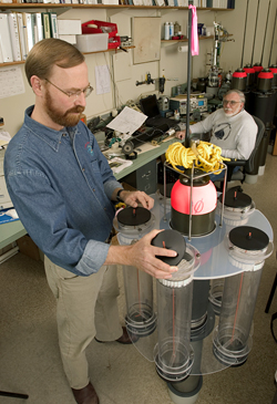 Ken Buesseler examines a neutrally buoyant sediment trap (NBST), while engineer Jim Valdes looks on.