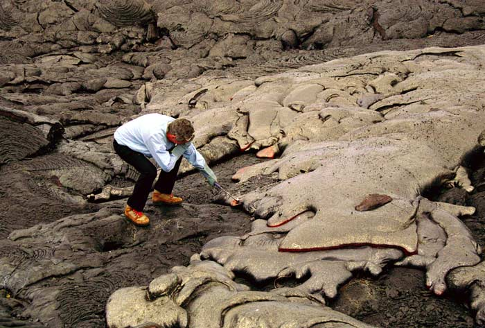 Stan Hart reaches to collect lava from an active flow on Kilauea in Hawaii.