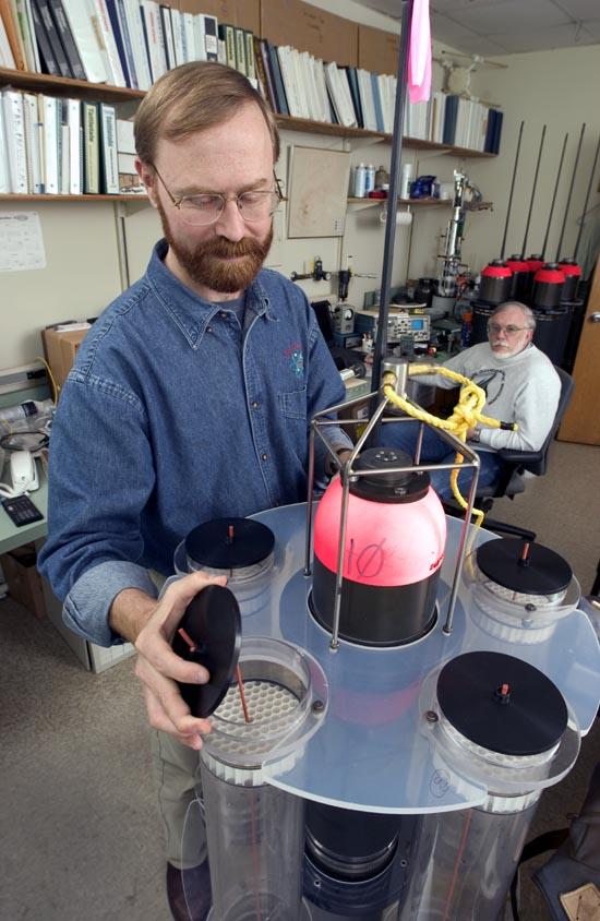 Marine chemist Ken Buesseler examines a neutrally buoyant sediment trap, while engineer Jim Valdes looks on.