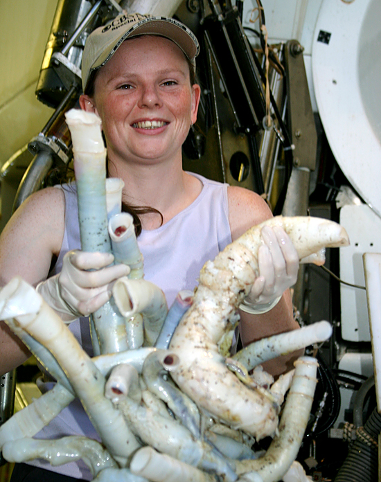 Rhiann Waller holding a bundle of tubeworms.