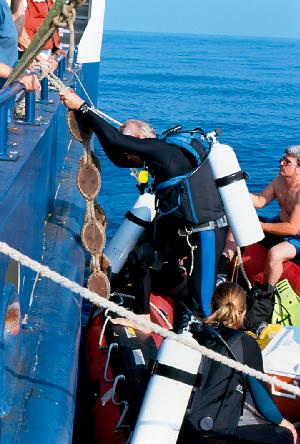 Larry Madin Stepping Down Into Achilles Inflatable Dive Boat. Kelly Rakow at the stern.
