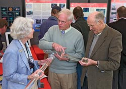 Ocean Life Institute Director Larry Madin (center) displays jellyfish to Lisina and Frank Hoch at the WHOI Trustees meeting in May.