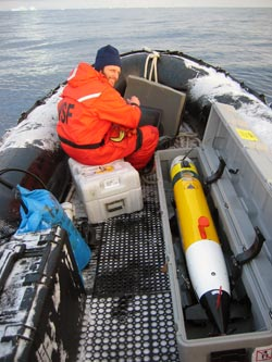 Greg Packard, in an inflatable boat, prepares to launch a REMUS (Remote Environmental Monitoring UnitS), to measure ocean bottom depths in a pre-determined area and pattern around Palmer Station, part of a 5-week survey resulting in a new chart of the area. (Photo by Keith von der Heydt, WHOI)