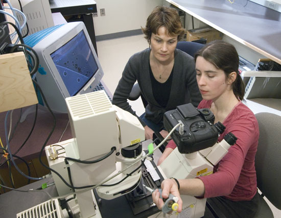 Sheri Simmons, with advisor Katrina Edwards looking on, prepares samples of pond water to view bacterial inhabitants under a microscope.