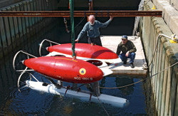 Before ABE's first deployment, ABE's inventors, Al Bradley (left) and Dana Yoerger tested the autonomous underwater vehicle in the test well at the WHOI dock in Woods Hole.