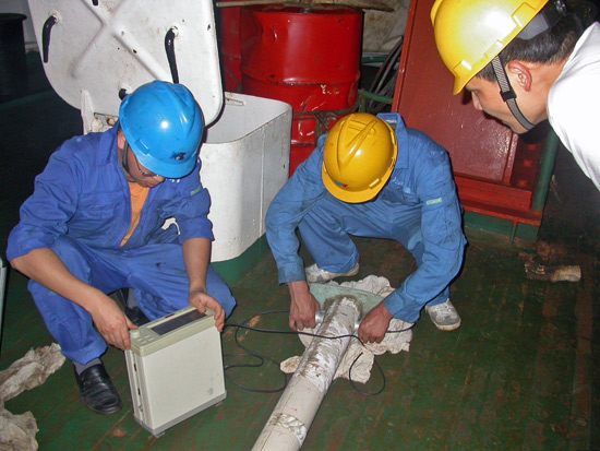 WHOI scientist Jian Lin (right) looks at a sediment core just retrieved from the site of the seafloor earthquake off Sumatra that caused the 2004 Indian Ocean tsunami.
