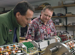 Engineer Andy Bowen (left) of the WHOI Deep Submergence Laboratory and Chris German, chief scientist of the National Deep Submergence Facility, inspect components for a WHOI deep-sea vehicle. (Photo by Tom Kleindinst, Woods Hole Oceanographic Institution)