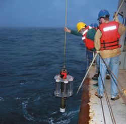 WHOI biogeochemist Ken Buesseler (blue hat) and engineer Jim Valdes (yellow hat) deploy a Neutrally Buoyant Sediment Trap for a three-day mission in the depths of the North Pacific Ocean in 2005. The instrument collects ?marine snow.?