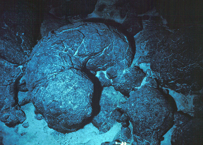 "Magma erupting at the seafloor often forms ""pillow"" lava. It forms when the molten rock, at temperatures of 2,200°F or 1,200°C, hits 35°F (2°C) seawater."