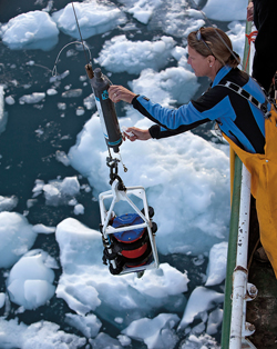 Physical oceanographer Ruth Curry draws a water sample from the bottom of Sermilik Fjord.