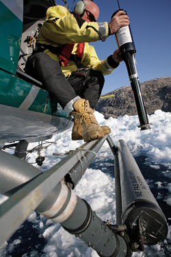 WHOI mooring engineer Jim Ryder aims an XBT at a patch of open water in Kangerdlugssuaq Fjord