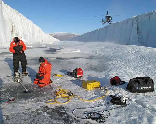 Fiamma Straneo (kneeling) and colleagues to drill through it to sample water within the fjord below.