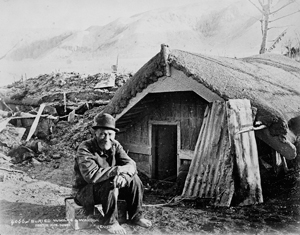 Maori man in front of buried house after eruption of Mt. Tarawera