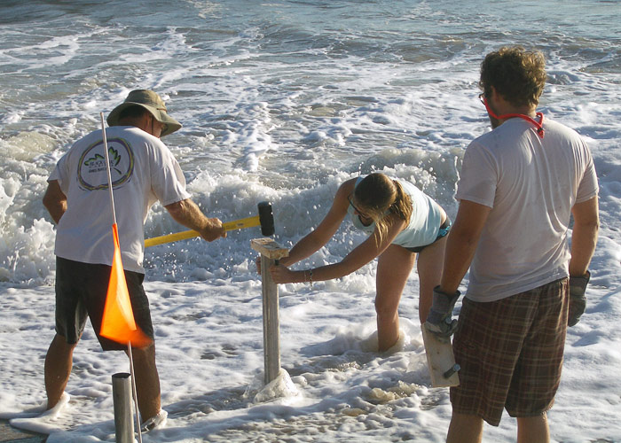 Worker hammers core tube into beach