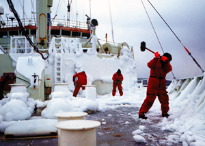Bundled-up crew members whack at ice on the deck of Knorr