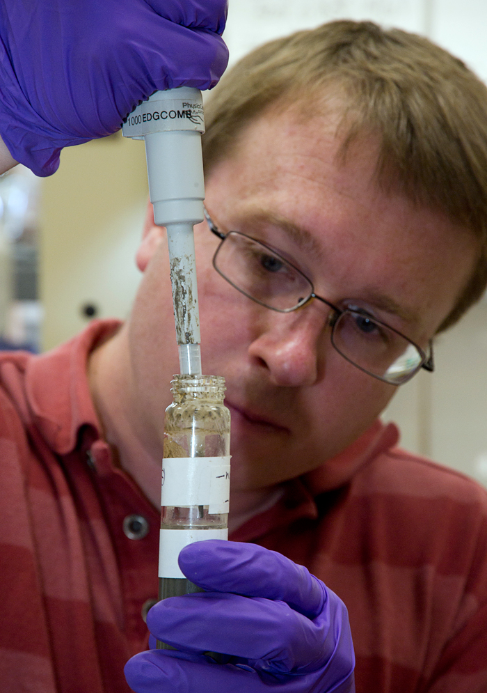 research associate Dave Beaudoin uses a pipet to collect microbes from a test tube