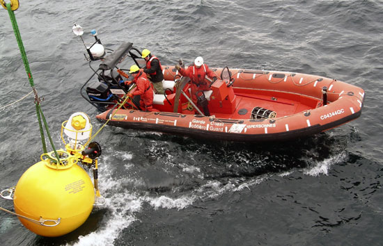 Mariners from the Canadian Coast Guard icebreaker Pierre Radisson use an inflatable boat to deploy a mooring equipped with an Arctic Winch, the white and yellow device on top.