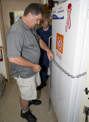 Bob Nelson with the locked refrigerator where Deepwater Horizon samples were held before processing