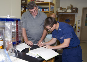 Bob Nelson and Coast Guard officer sign chain-of-custody papers for the sample from Deepwater Horizon