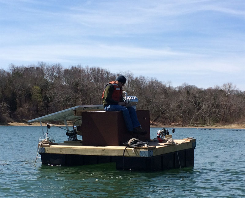 Biologist Mike Brosnahan atop the PhytO-ARM raft in Nauset Marsh in Eastham, Mass