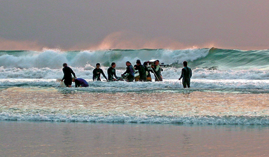 Researchers carry an instrument tower into the surf.