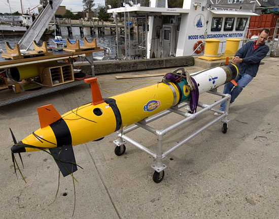 Greg Packard prepares an autonomous underwater vehicle (AUV) REMUS equipped with synthetic aperture sonar for testing off the WHOI dock. Different sensors can be added to REMUS depending on the mission. The coastal research vessel Tioga is in the background.