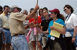Researcher Jim O'Connell shows teachers, participating in a workshop, how to measure the shoreline depth.