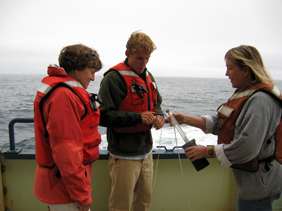 Amy, graduate student Dave Sutherland, and unidentifiied crew member collect a water sample.