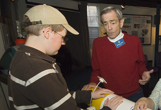WHOI volunteer Sheldon Holzer showing a student a REMUS vehicle at the WHOI exhibit center.