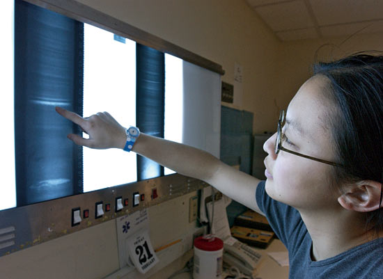 Mea Cook examines an X-ray image of a sediment core