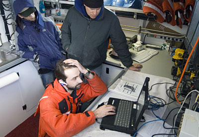 Andrey is on the phone with Greg Packard, REMUS expert from the WHOI Applied Ocean Physics and Engineering Department, getting some technical advice at sea