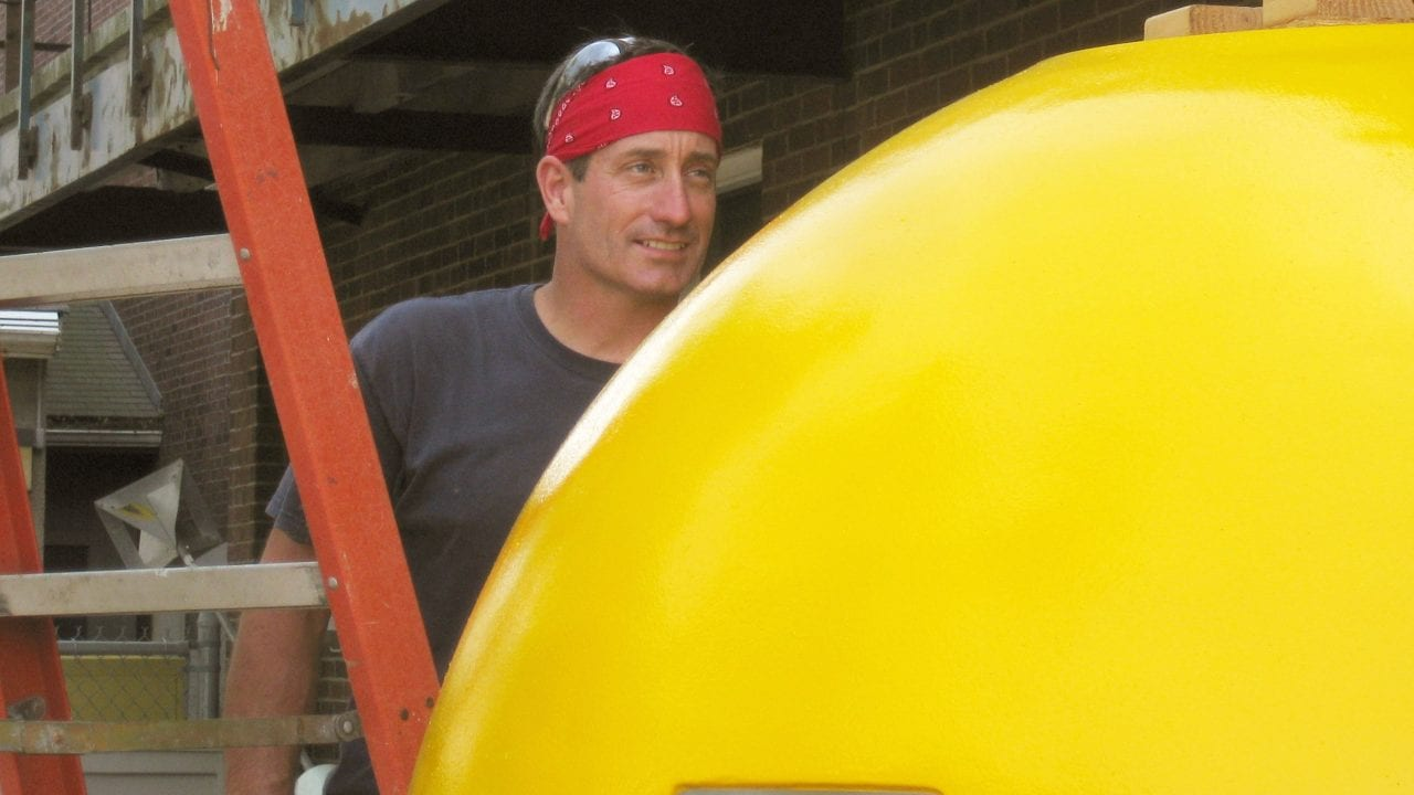 Joe Fellows prepares a syntactic sphere outside the Mooring Lab