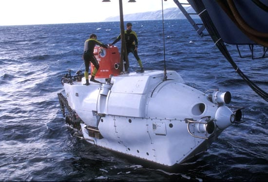 Support swimmers stand by to remove the lift lines as Alvin goes into the water on a cold water launch. (Woods Hole Oceanographic Institution)