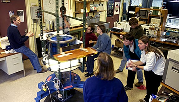 Dave (left) explaining the dynamics of a laboratory demonstration to graduate students.. (Woods Hole Oceanographic Institution)