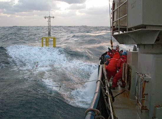 Researchers and crew members struggle to deploy a spar buoy in rough seas during a January 2006 cruise of R/V Atlantis in the North Atlantic.
